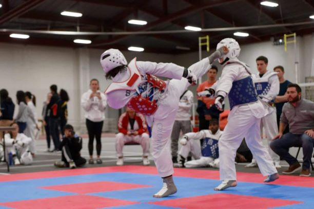 Omer Fahri Onder kicking an opponent at the MIT taekwondo competition